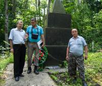 Представители комиссии возле памятника большой могилы в лесу